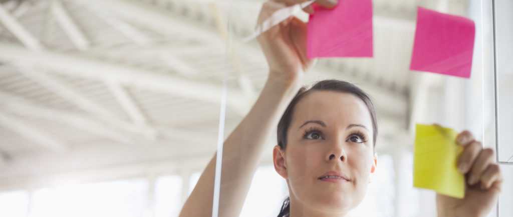 Woman puts sticky notes on glass wall in office.