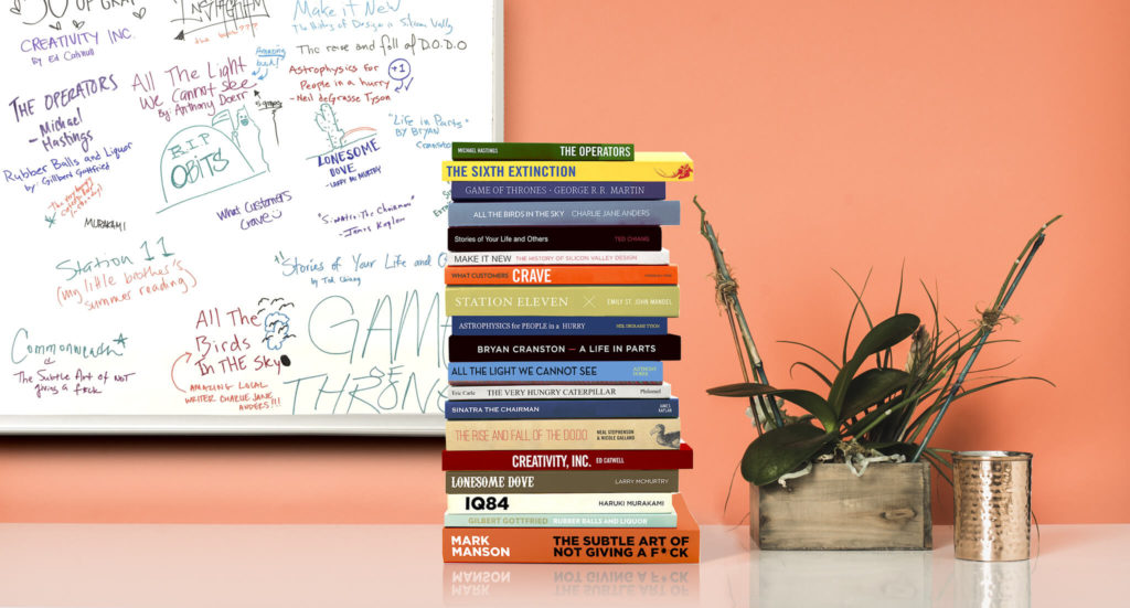 A stack of books in front of a whiteboard and plant