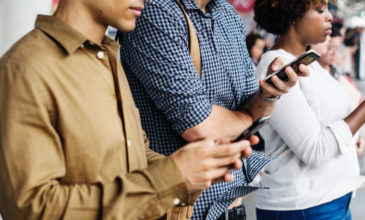 Three individuals on their phones outside