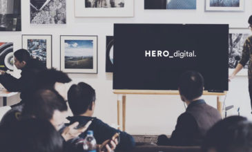 Group of people looking at tv screen with Hero Digital logo on it