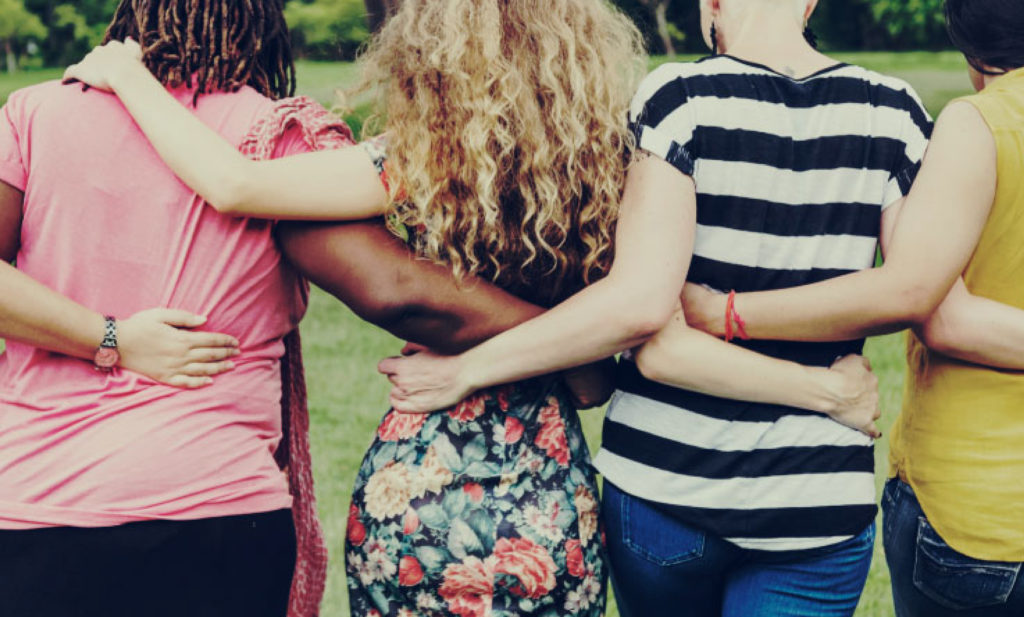 Backs of four women with arms around each other