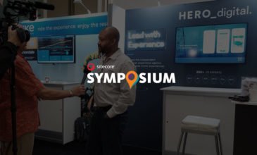 Sitecore Symposium logo over photo of Carl Agers being interviewed by Hero Digital booth.