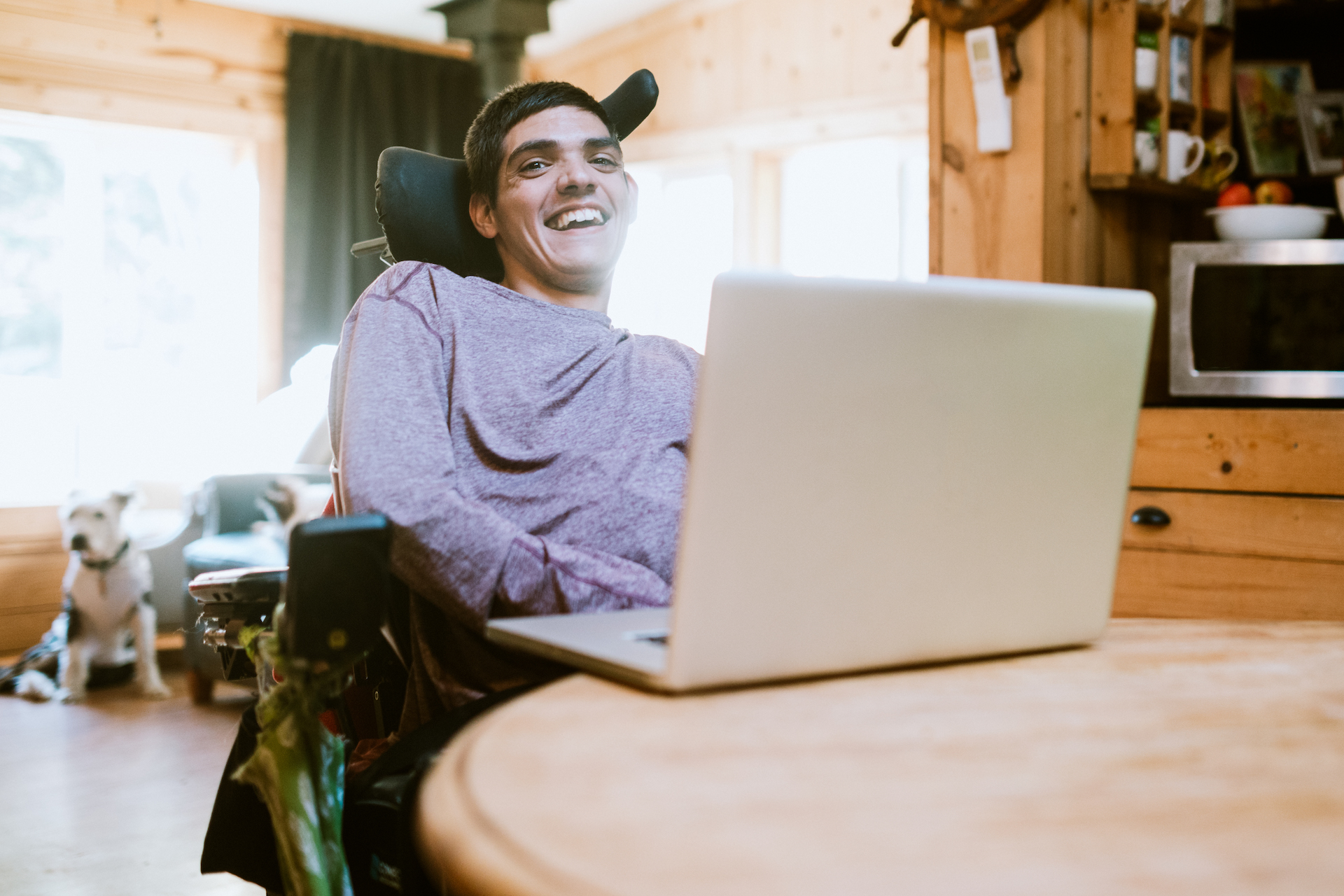 Man with cerebral palsy researches something on his laptop, using voice recognition assistive technology