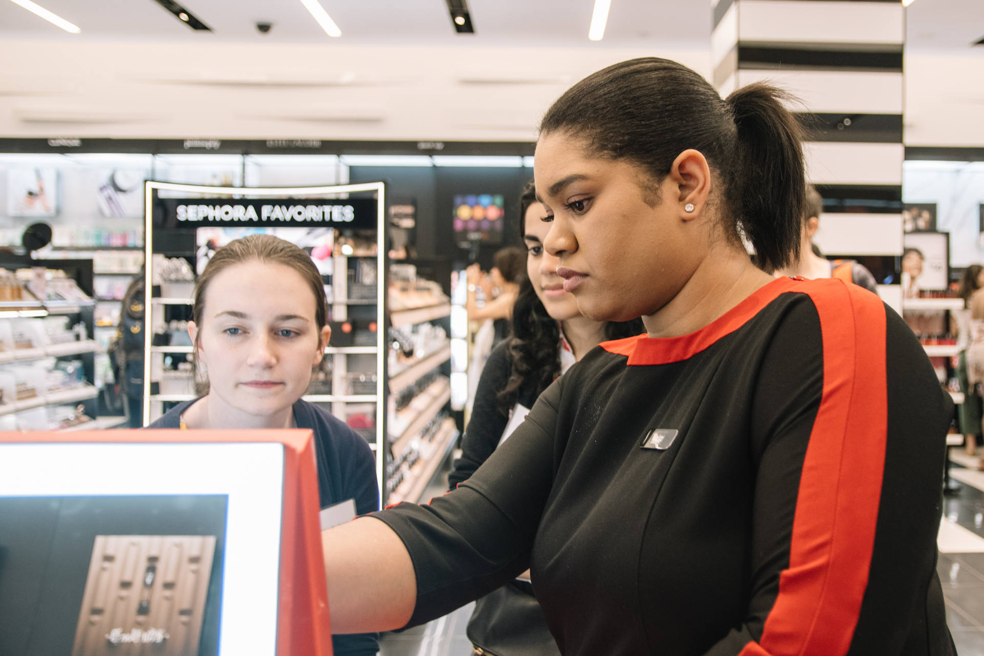 Sephora employee showing a customer how to use digital personalization kiosk