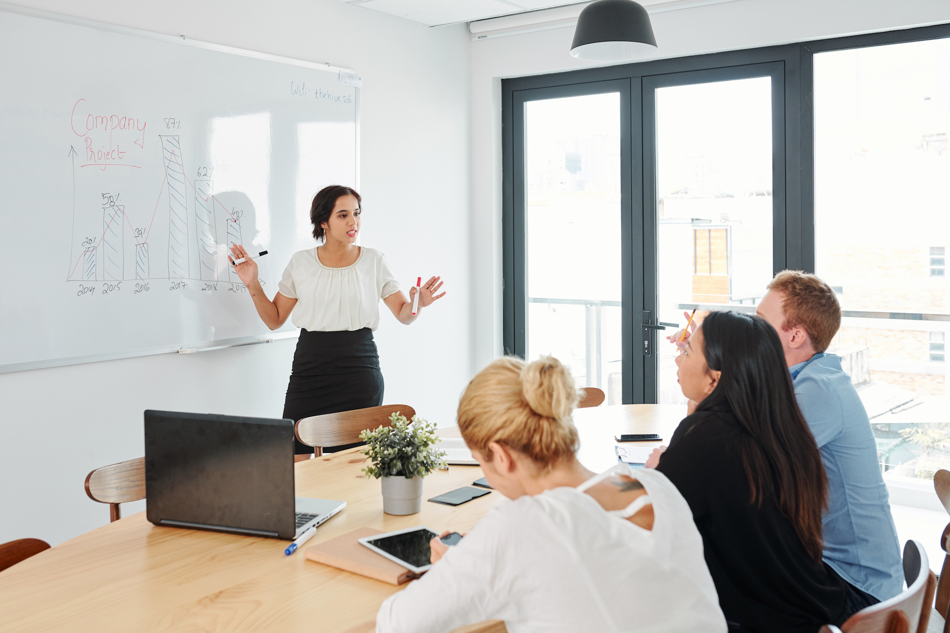 Businesswoman standing near the whiteboard and giving presentation on business strategy