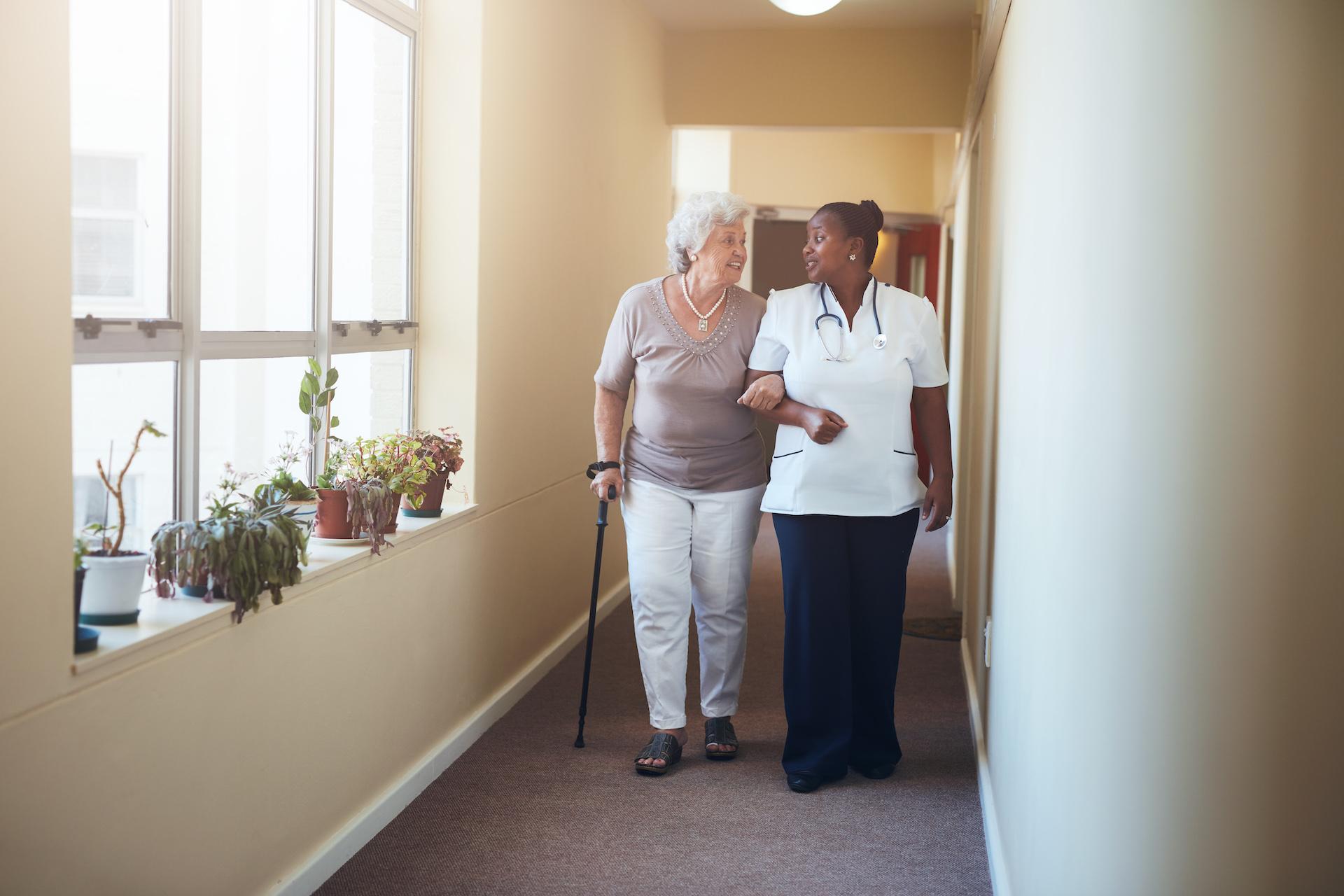Senior woman walking with her nurse at nursing home