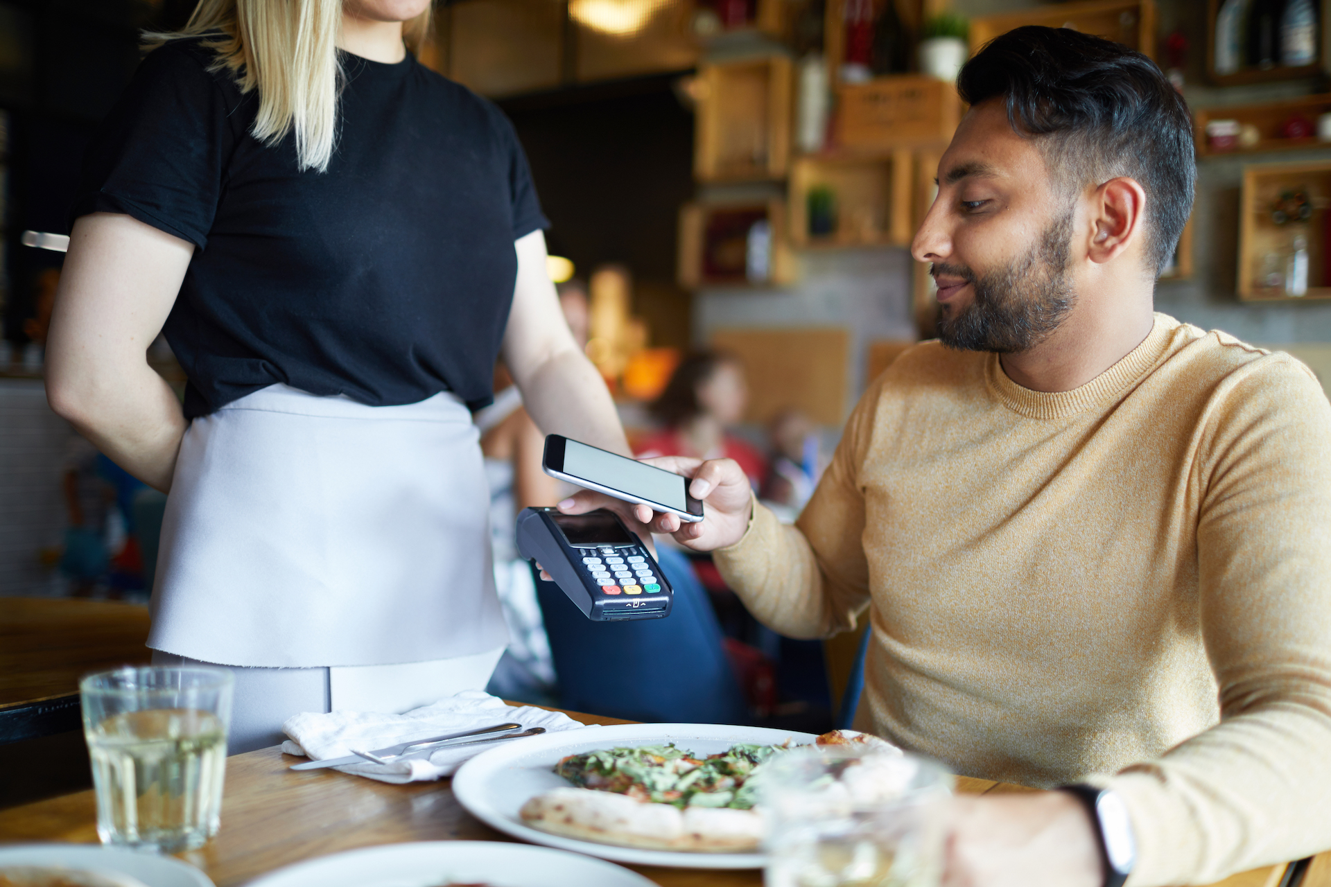 Young man holding his smartphone over payment machine while sitting by table in cafe during lunch