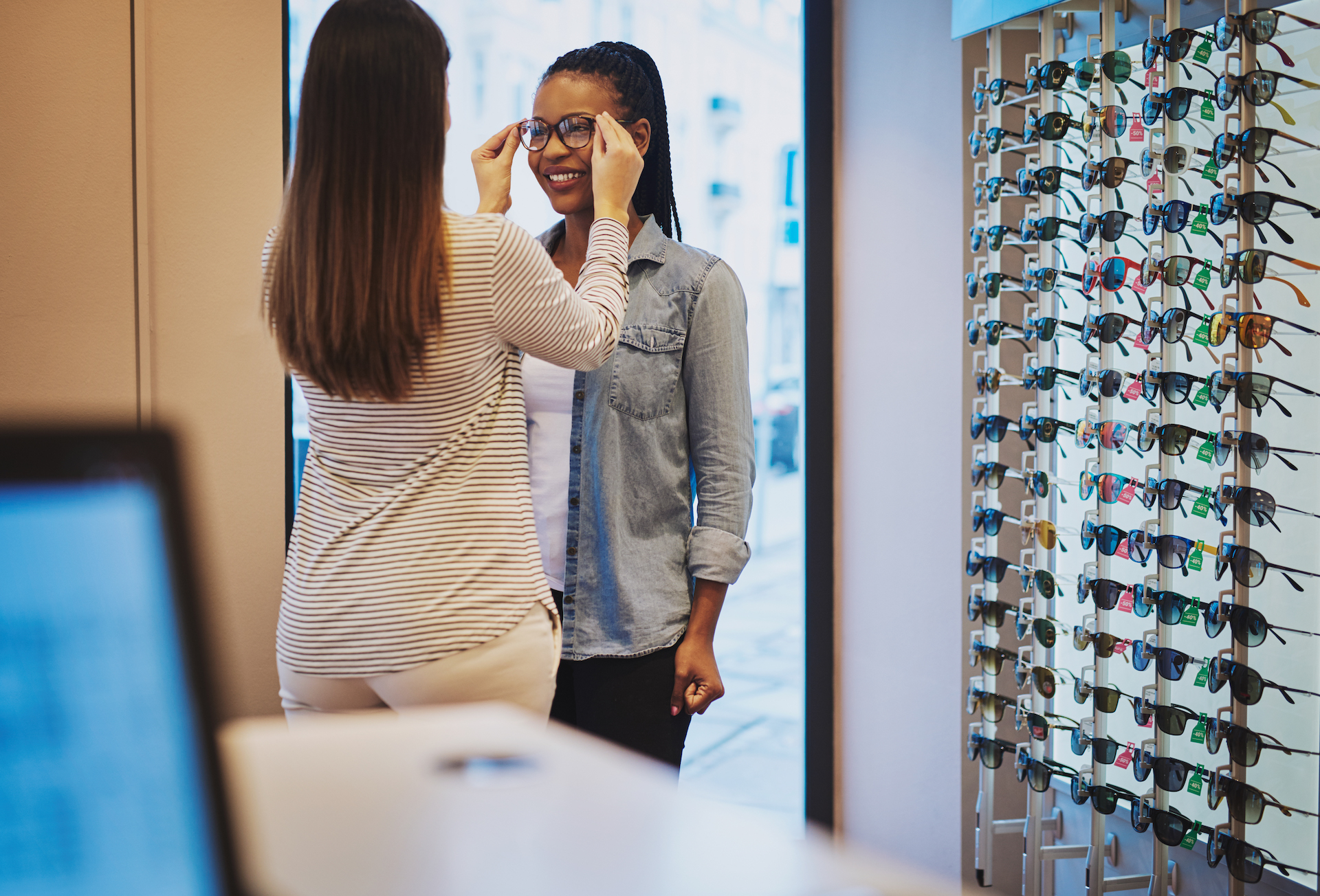 Optometrist helping a patient to select eyeglasses