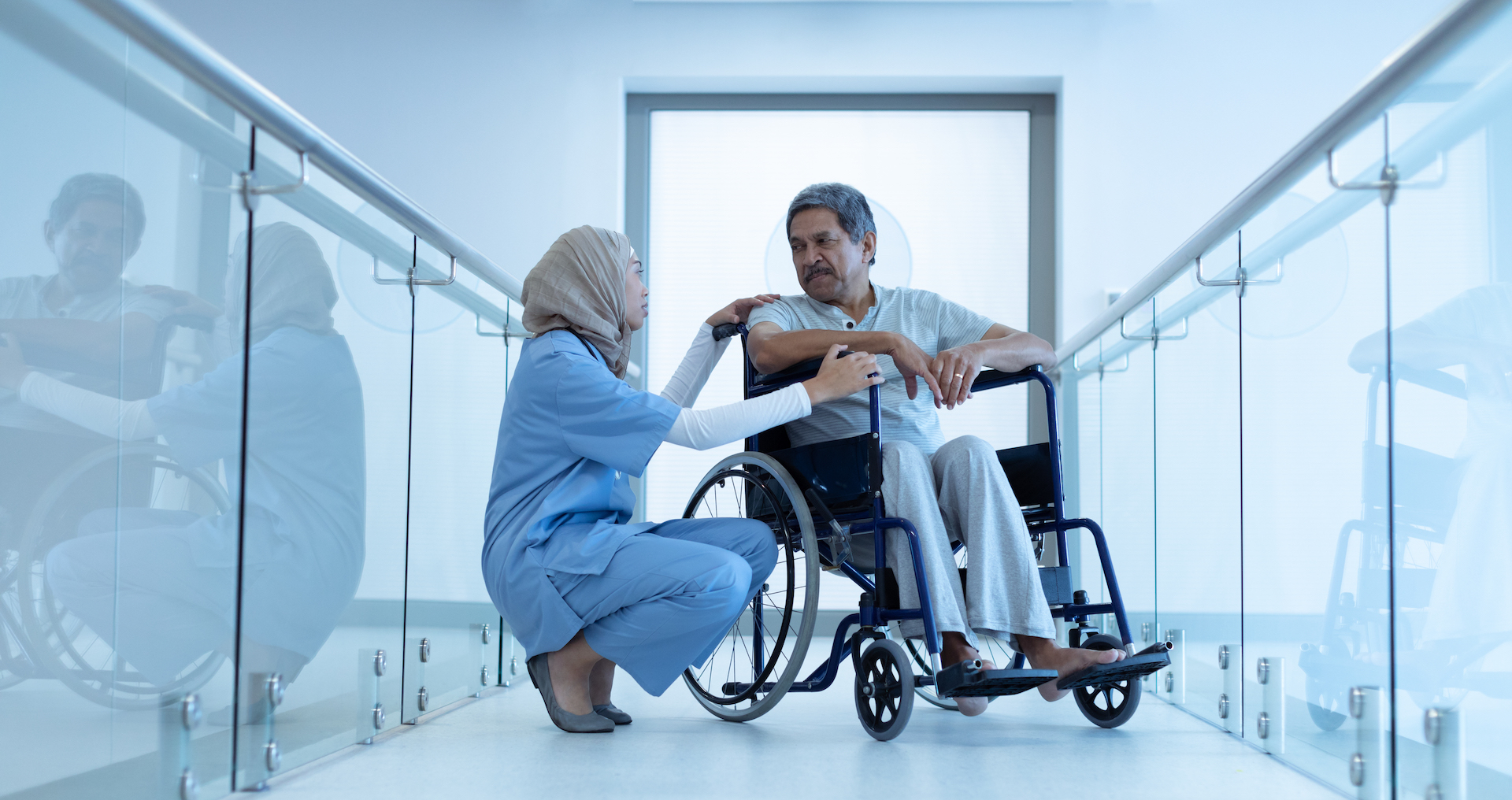 Female doctor in hijab interacting with male patient in wheelchair in the corridor at hospital