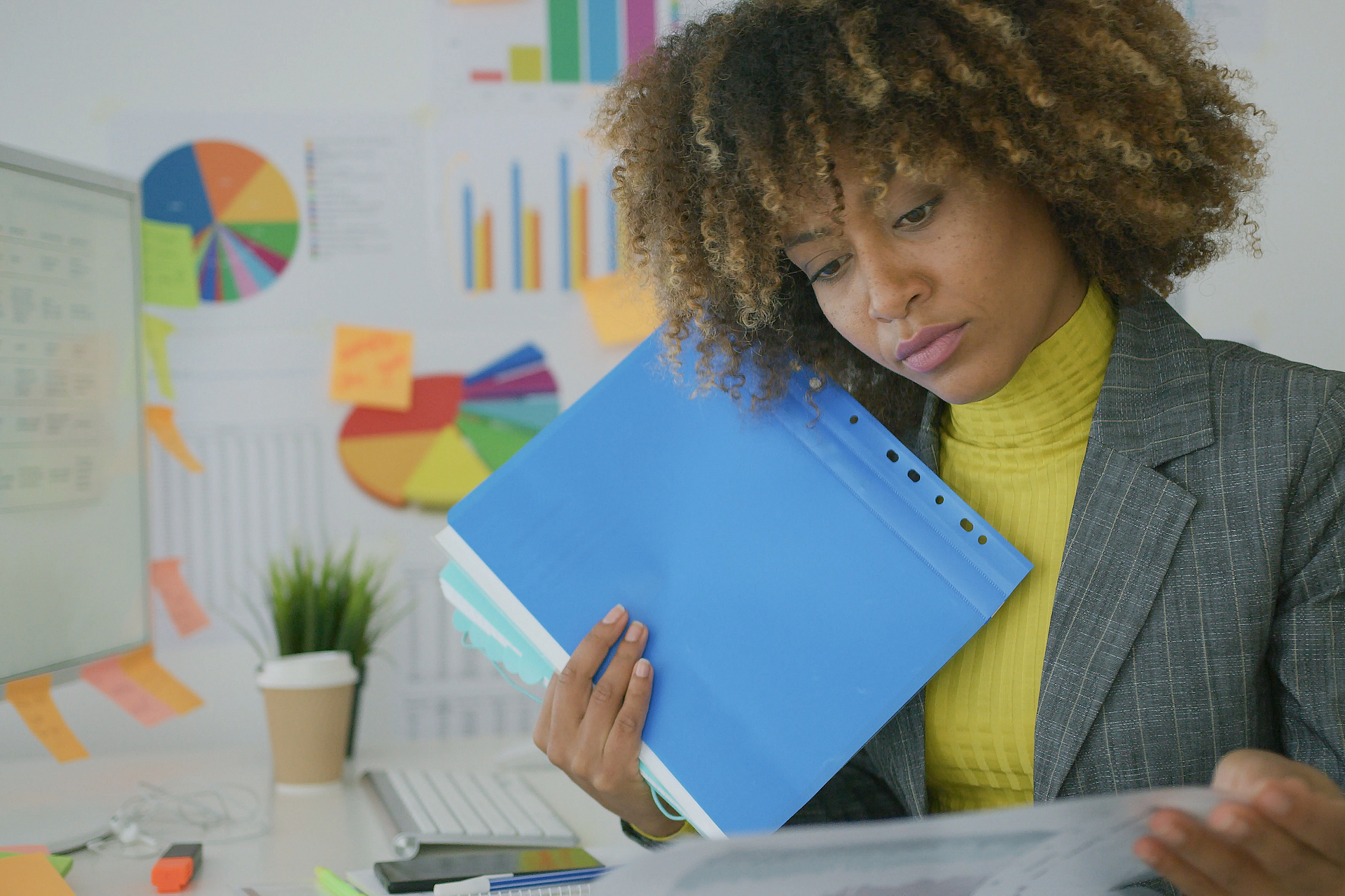 Businesswoman sitting at desk and looking through papers in files with data
