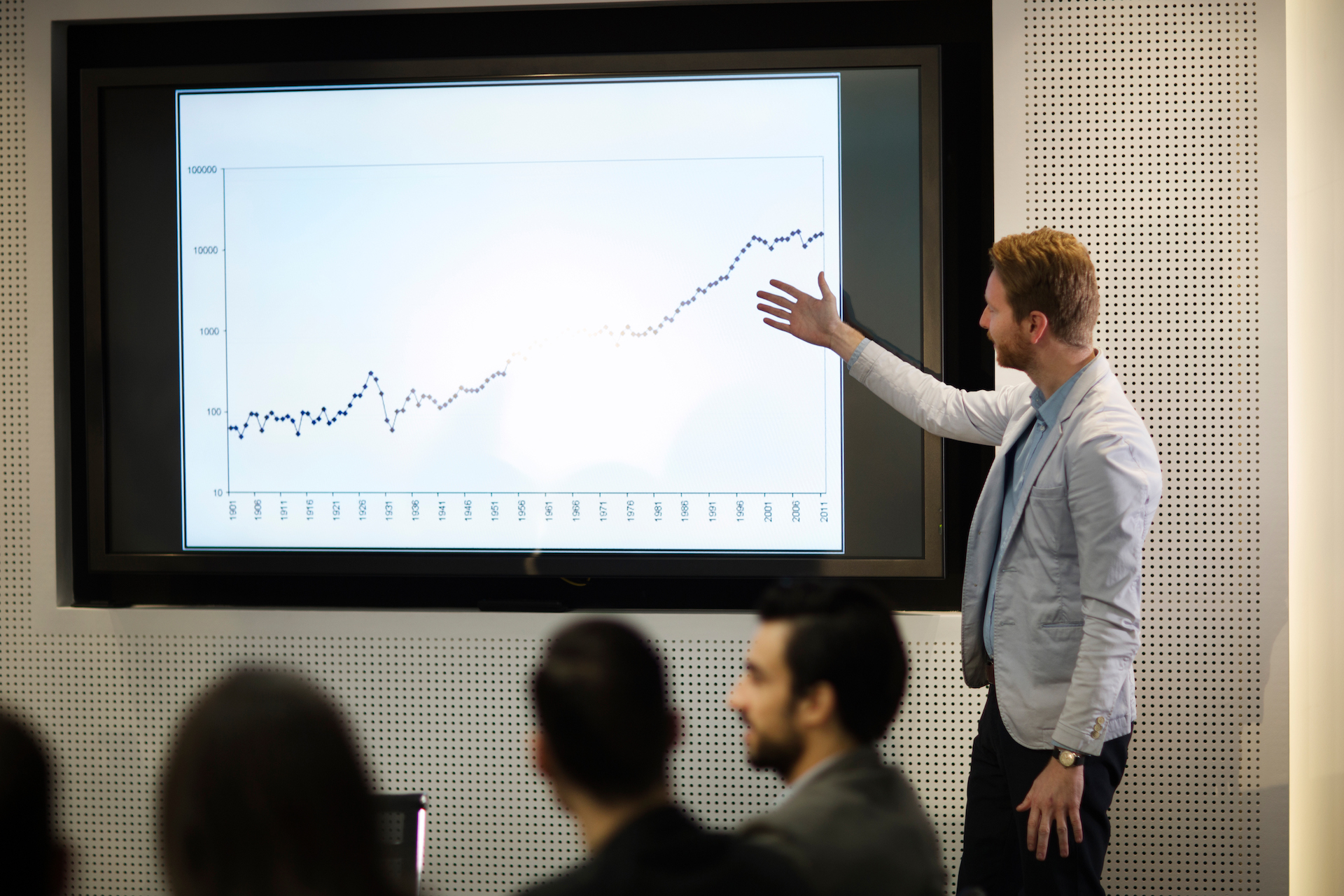 Young businessman showing data graph presentation to his colleagues in conference room
