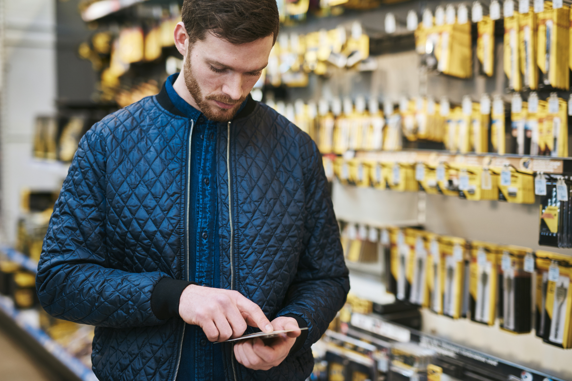Young man checking a text message on his mobile phone as he shops in a hardware store for DIY supplies