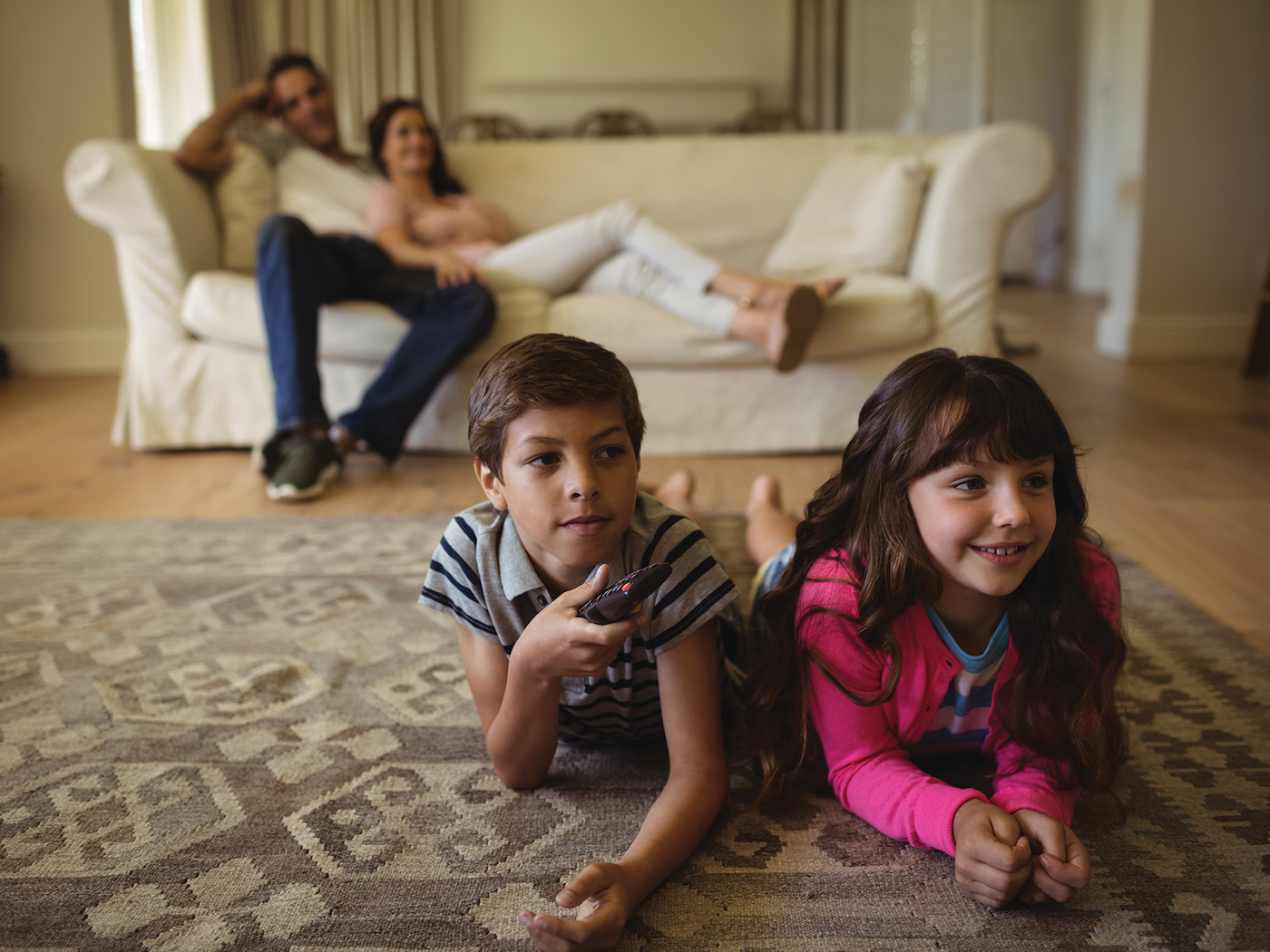 Two children lounge on floor of living room watching TV with parents behind them on couch