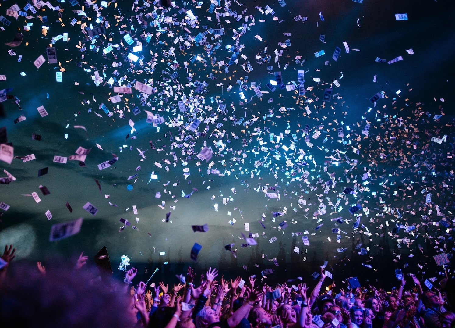 People standing below confetti flying in the air